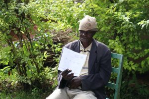 The Water Project:  An Elderly Man Reading Through The Pamphlet