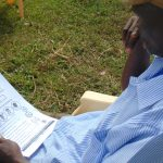 The Water Project: Ulagai Community, Rose Obare Spring -  An Elder Reads An Informational Pamplet
