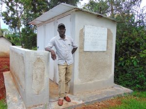 The Water Project:  The Deputy Head Teacher Poses With The Latrines