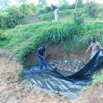 The Water Project: Shikangania Community, Abungana Spring -  Laying Thick Plastic Tarp Over Stones