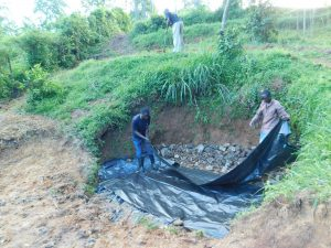 The Water Project:  Laying Thick Plastic Tarp Over Stones