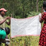 The Water Project: Emachembe Community, Mukabane Spring -  Installing The Prevention Reminder Chart