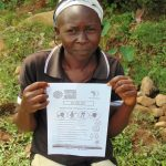 The Water Project: Ulagai Community, Rose Obare Spring -  Community Member Showing Pamphlet In Her Dholuo Language