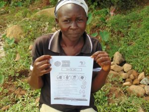 The Water Project:  Community Member Showing Pamphlet In Her Dholuo Language