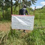 The Water Project: Mukoko Community, Mshimuli Spring -  Trainer Erick Mounting The Chart At The Spring