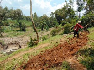 The Water Project:  Digging Cut Off Drainage Above Spring