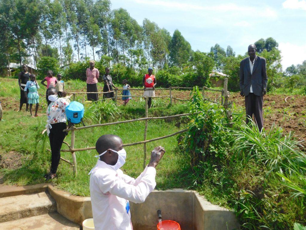 The Water Project : 4-covid19-kenya19178-trainer-protus-demonstrates-handwashing