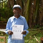 The Water Project: Ibinzo Community, Lucia Spring -  An Elder Holds Pamphlet