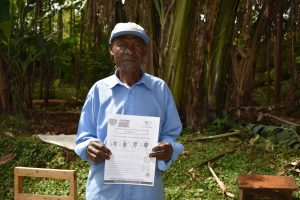 The Water Project:  An Elder Holds Pamphlet