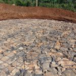 The Water Project: Kapsaoi Primary School -  Setting Tank Foundation With Stones And Wire