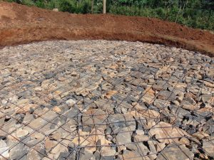 The Water Project:  Setting Tank Foundation With Stones And Wire