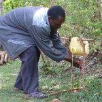 The Water Project: Emachembe Community, Hosea Spring -  Mr Henry Showing How To Use The Modified Leaky Tin