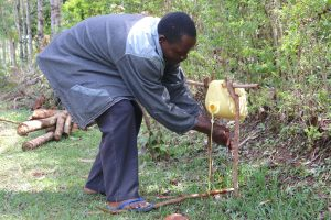 The Water Project:  Mr Henry Showing How To Use The Modified Leaky Tin