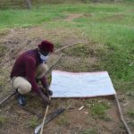 The Water Project: Bukhakunga Community, Ngovilo Spring -  Sir Erick Nailing The Chart Onto The Poles