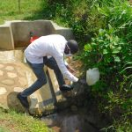 The Water Project: Eshiakhulo Community, Kweyu Spring -  Protus Rinses His Hands At The Leaky Tin