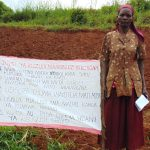 The Water Project: Shitaho Community B, Isaac Spring -  Standing With Chart Placed At The Spring