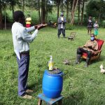 The Water Project: Mukhangu Community, Okumu Spring -  Community Elder Demonstrates Handwashing