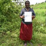 The Water Project: Mukoko Community, Mshimuli Spring -  A Community Member Holding Up A Covid Pamphlet