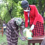 The Water Project: Emachembe Community, Hosea Spring -  Trainer Shigali Helps A Woman Wash Her Hands With A Leaky Tin