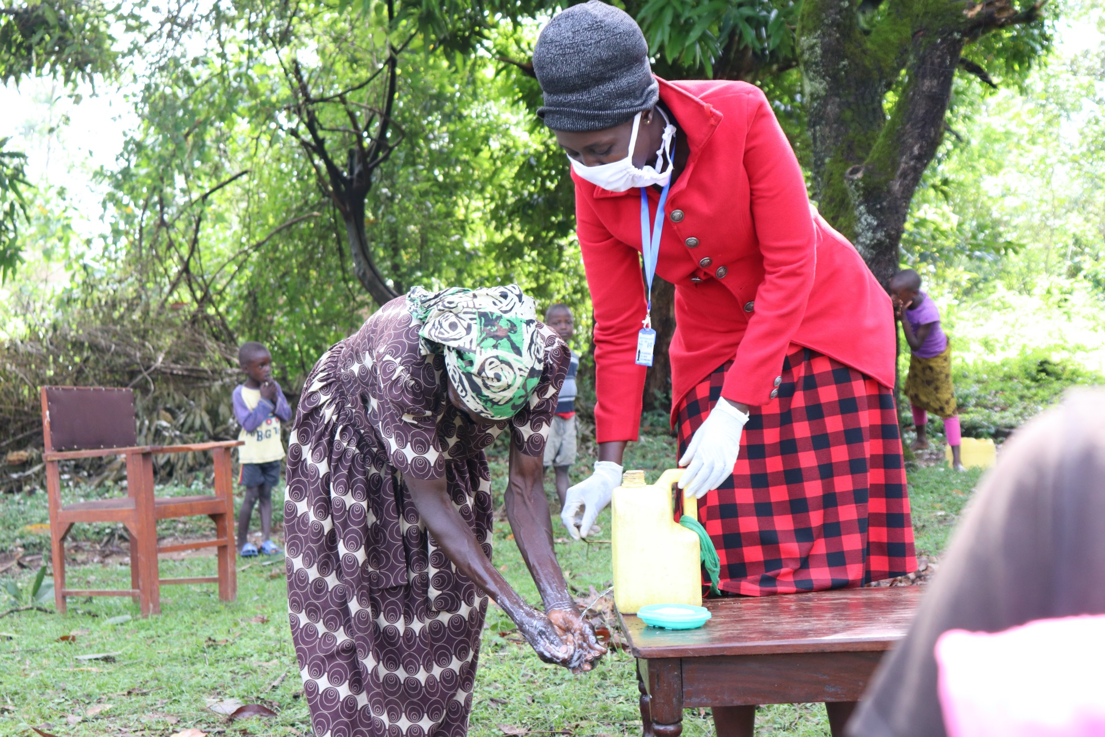 The Water Project : 6-covid19-kenya18145-trainer-shigali-helps-a-woman-wash-her-hands-with-a-leaky-tin