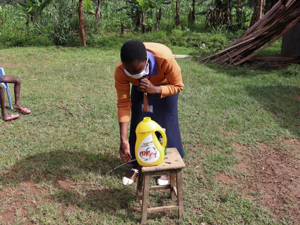 The Water Project : 6-covid19-kenya18154-trainer-amulavu-demonstrating-handwashing