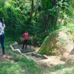 The Water Project: Mungakha Community, Asena Spring -  Trainers Demonstrate Social Distancing While Fetching Water