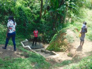The Water Project:  Trainers Demonstrate Social Distancing While Fetching Water