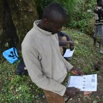 The Water Project: Ingavira Community, Laban Mwanzo Spring -  Reading An Informational Pamphlet