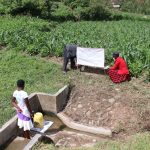 The Water Project: Emachembe Community, Hosea Spring -  Installing Reminder Chart At Spring