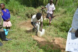 The Water Project:  A Boy Helping To Make A Leaky Tin