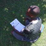 The Water Project: Shihingo Community, Mangweli Spring -  A Child Follows The Covid Sensitization Using Issued Pamphlets