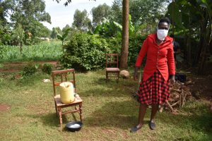 The Water Project:  Covid Facilitator Wearing Protective Gear Next To Handwashing Station