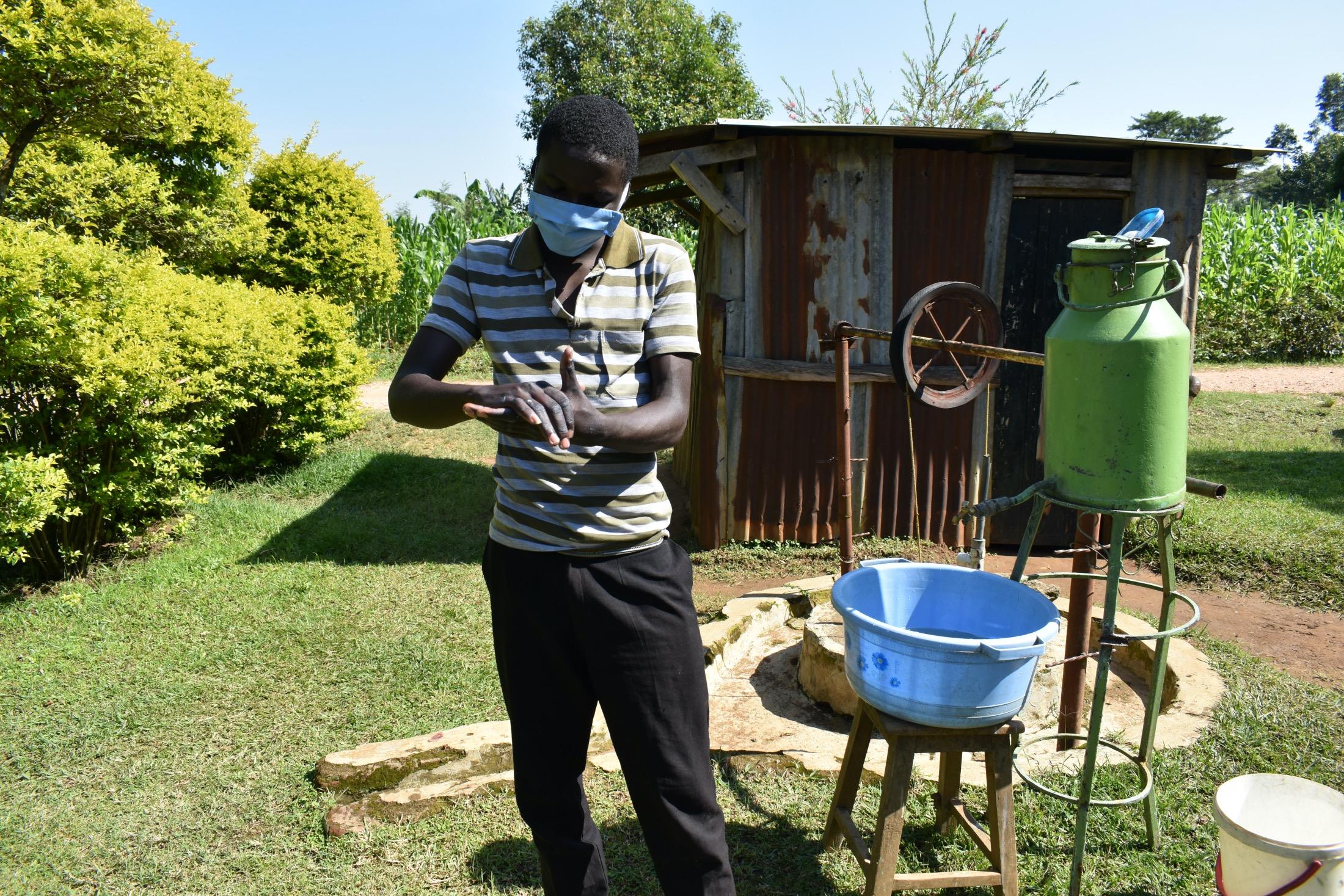 The Water Project : covid19-kenya19095-a-community-member-demonstrating-handwashing