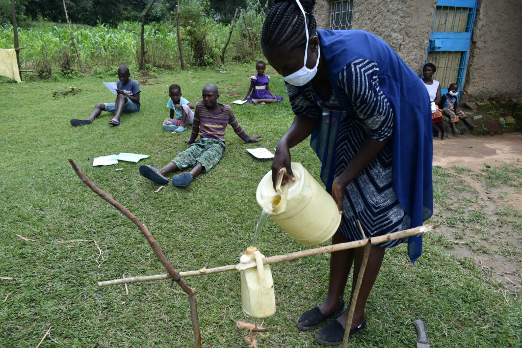 The Water Project : covid19-kenya19105-refilling-handwashing-container
