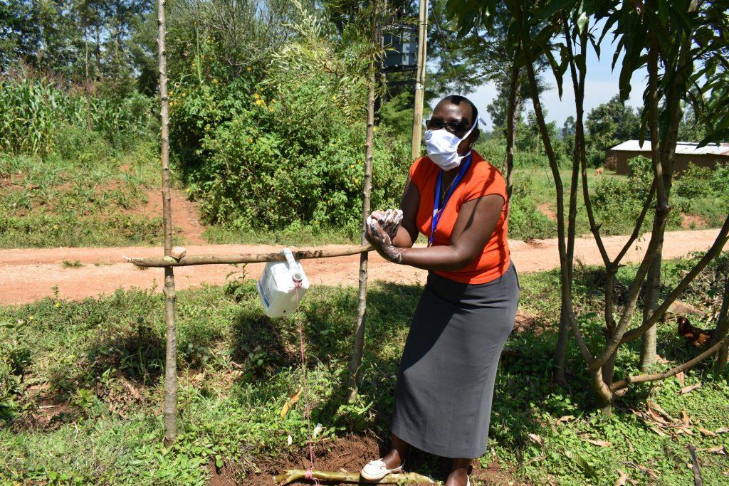The Water Project : covid19-kenya19129-facilitator-demonstrates-proper-handwashing