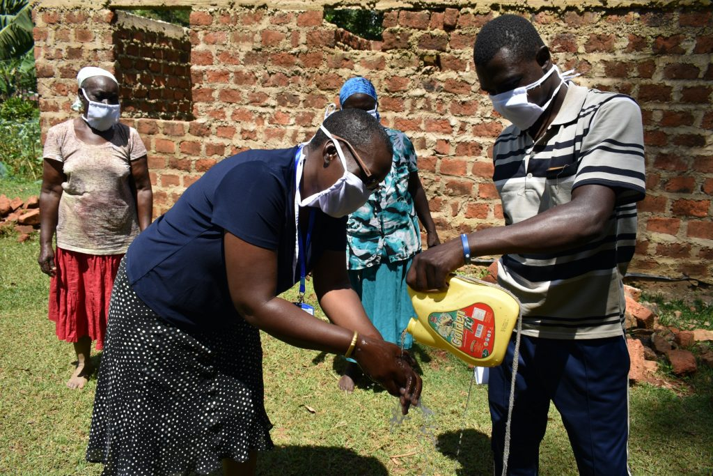 The Water Project : covid19-kenya19162-using-a-leaky-tin-in-handwashing