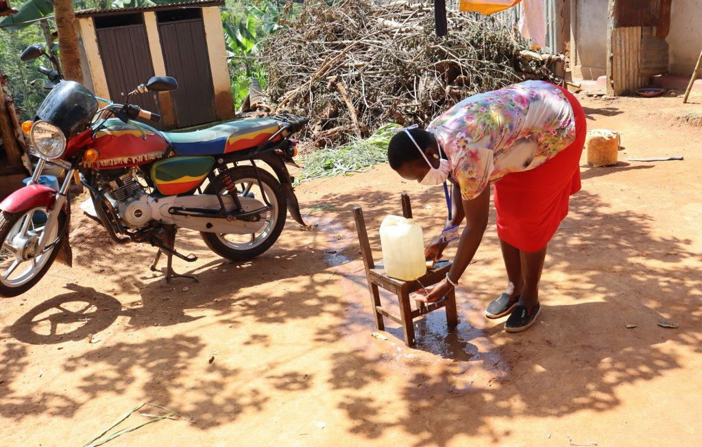 The Water Project : covid19-kenya19167-demonstration-of-using-a-leaky-tin-for-handwashing