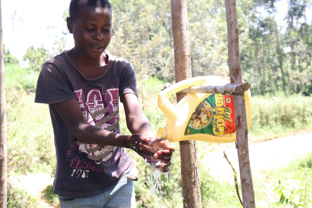 The Water Project : covid19-kenya4749-a-boy-demonstrates-handwashing-1