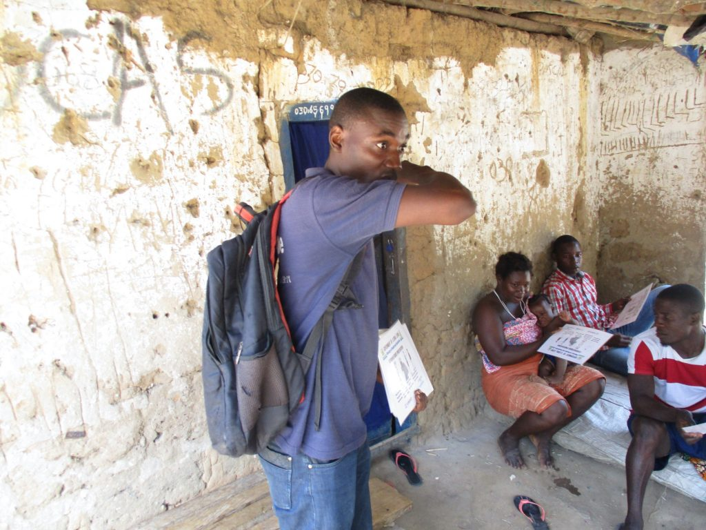 The Water Project : covid19-sierraleone5050-trainer-shows-proper-way-to-cover-a-cough