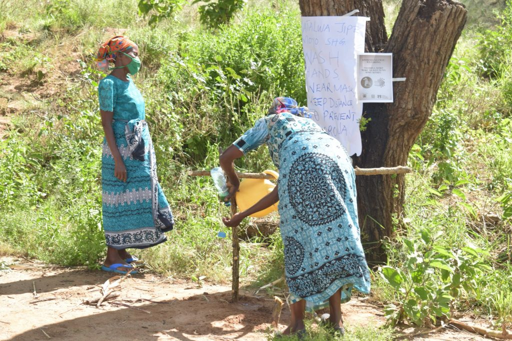 The Water Project : kenya18221-covid19-setting-up-handwashing-station-and-sign