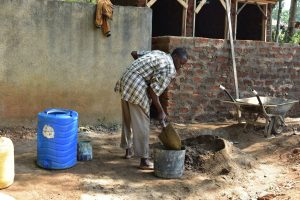 The Water Project:  Community Member Helps Mix Cement