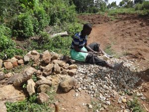 The Water Project:  A Community Mamber Breaks Stones Into Gravel