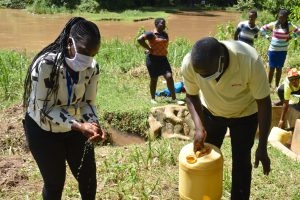 The Water Project:  A Community Member Helped Her Out A Bit