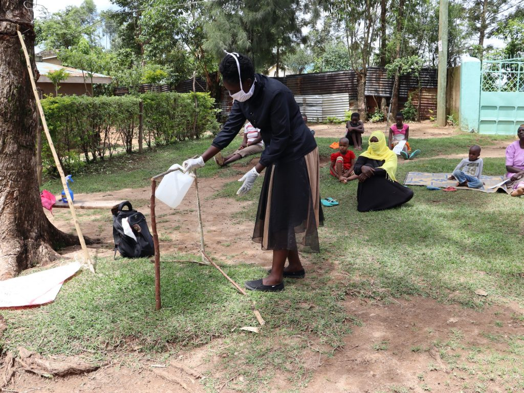 The Water Project : 11-covid19-kenya18112-the-facilitator-showing-how-effective-the-tippy-tap-is