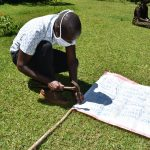 The Water Project: Musutsu Community, Mwashi Spring -  Sir Victor Nailing The Chart Onto The Poles