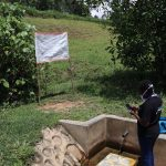The Water Project: Masera Community, Ernest Mumbo Spring -  Conducting Survey On Phone And Installed Chart At The Spring