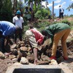 The Water Project: Mahira Community, Jairus Mwera Spring -  Backfilling With Stones