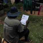 The Water Project: Masera Community, Ernest Mumbo Spring -  A Community Member Uses A Handout To Follow Trainings
