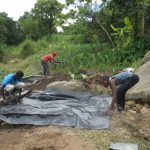 The Water Project: Mahira Community, Kusimba Spring -  Backfilling With Tarp Layer