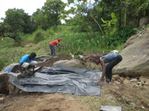 The Water Project:  Backfilling With Tarp Layer